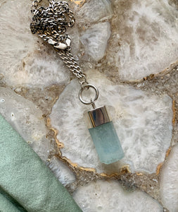 Aquamarine crystal talisman with sterling silver O ring attachment and curb chain on  geode background with seafoam colored silk.