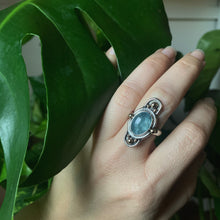 Load image into Gallery viewer, Oval aquamarine sterling silver ring with brass spheres and silver arches on top and bottom on hand in front of monstera plant.