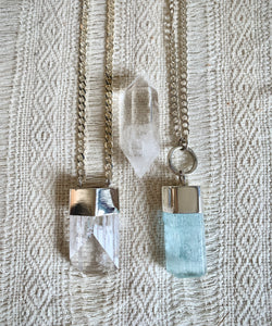 Aquamarine talisman and danburite talisman next to each other with double terminated quartz crystal on woven background.