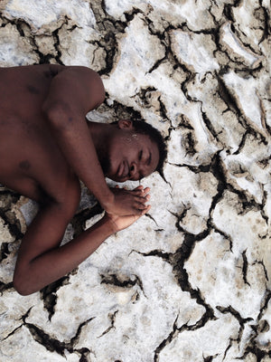 Exposed a picture showing a boy lying on the soil by Nana Yaw Oduro.