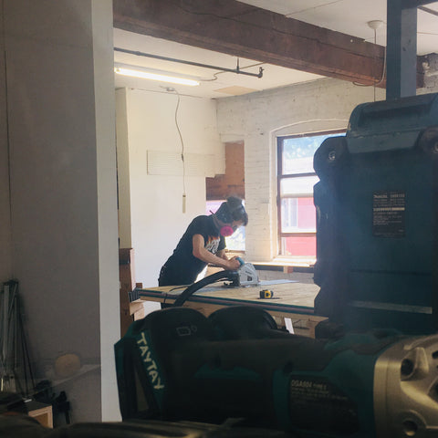 Shopdog co-founder and cabinetmaker, Taylor Cott wearing a mask at work while using a saw on a piece of wood.