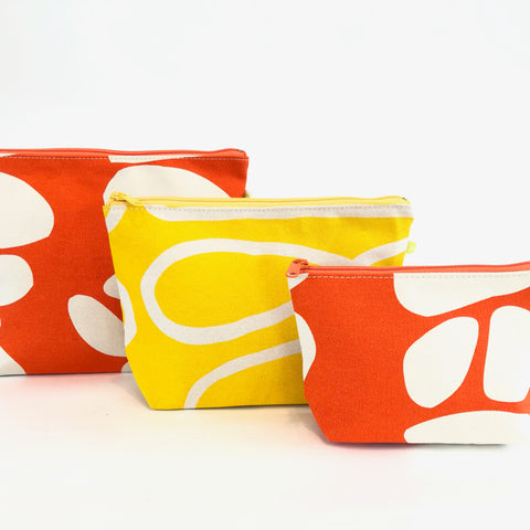 extra large and small travel pouch in totem orange, large travel pouch in loopy yellow