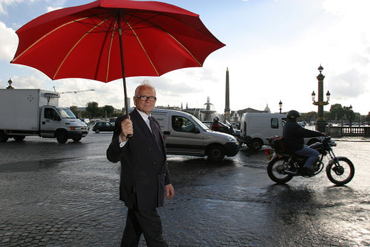 Rendezvous With Pierre Cardin. Pierre CARDIN fête 29 ans de développement dans l'Empire du milieu: se promenant place de la Concorde à PARIS abrité sous un grand parapluie rouge .. (Photo by Bruno Bachelet / Paris Match via Getty Images)