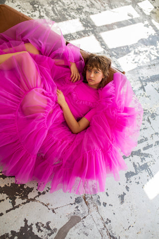 A tulle dress in fuchsia wit  layered ruffles, short sleeve and round neckline