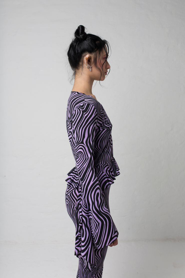 fashion brand BONDY photoshoot showcasing handmade AURORA abstract long-sleeve purple and black flare top on size small model, part of new collection DREY:MA. side view