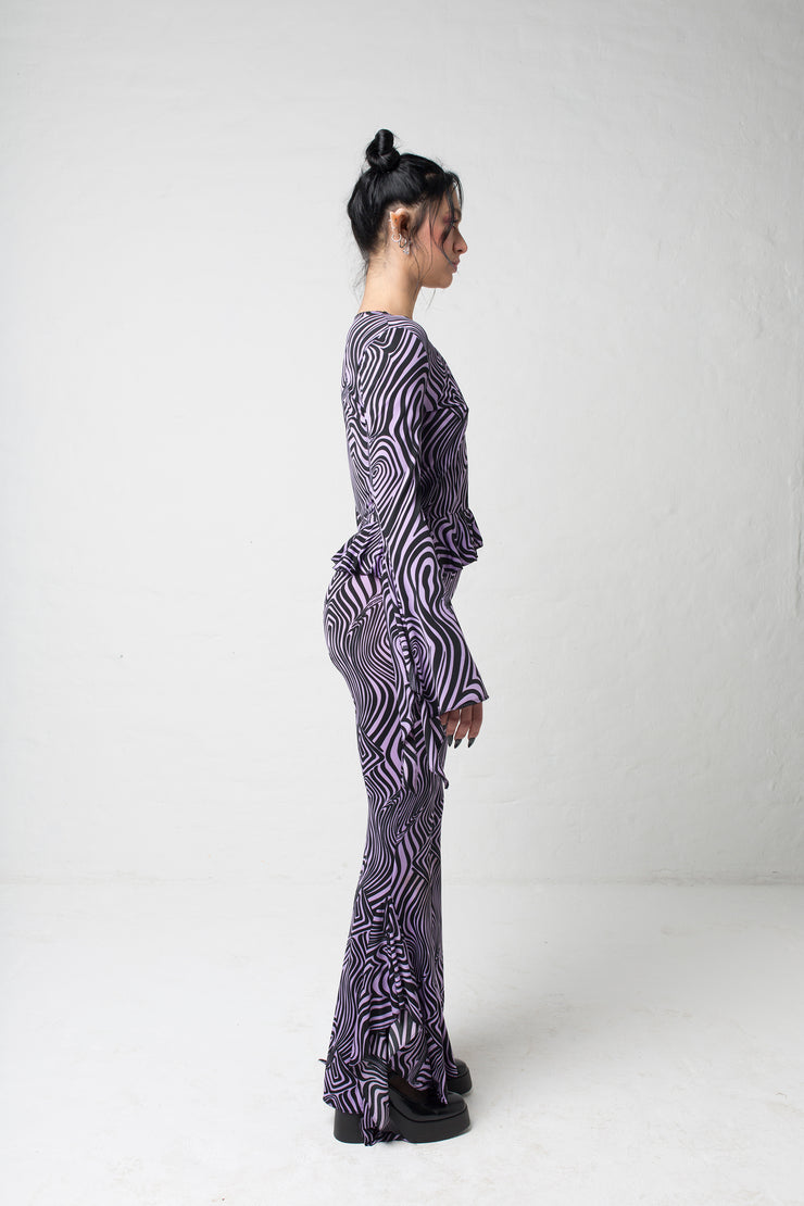 fashion brand BONDY photoshoot showcasing handmade AURORA abstract long-sleeve purple and black flare top on size small model, part of new collection DREY:MA. full body side view