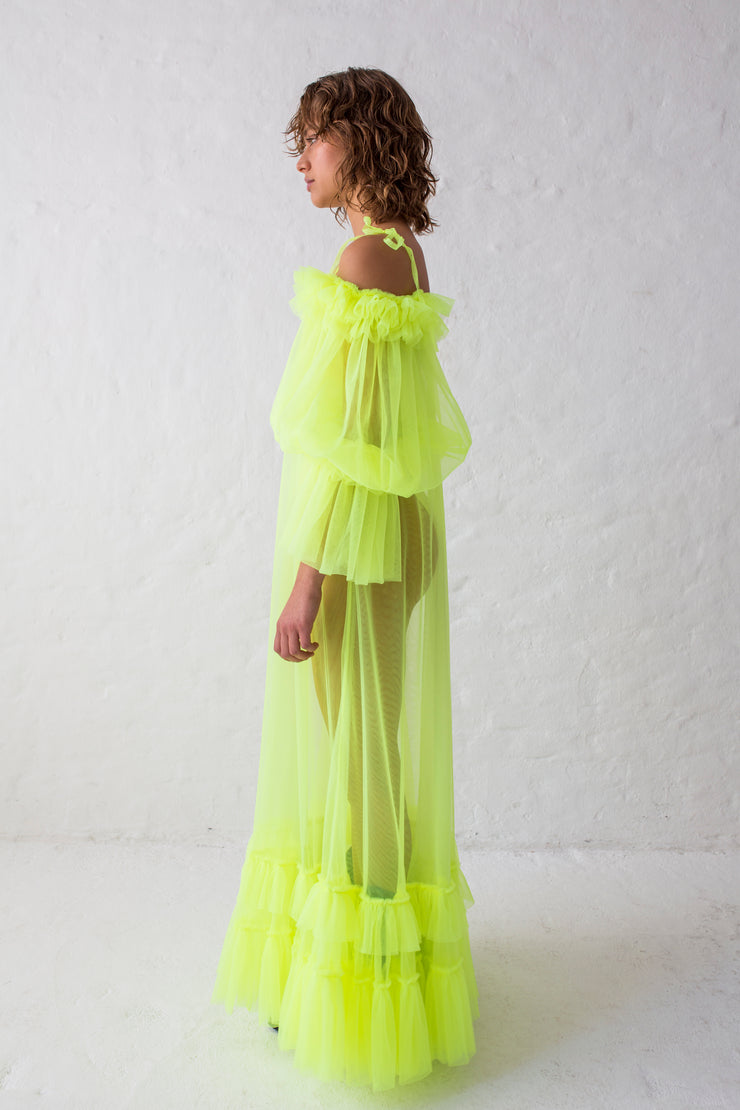 Flue yellow floor length evening gown with voluminous off-shoulder puffy sleeves and thin shoulder straps. Contrasted by sheer body and ruffled hem