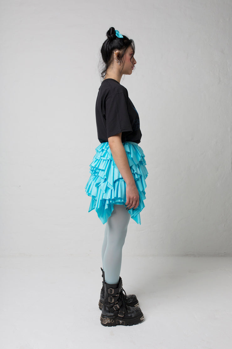 fashion brand BONDY photoshoot showcasing handmade CASSIA mini ruffle ice blue skirt shown on size small model, part of new collection DREY:MA. full body side view