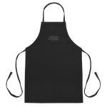 Black apron with embroidered words 'AS FOR ME AND MY HOUSE, WE WILL SERVE BRISKET'.