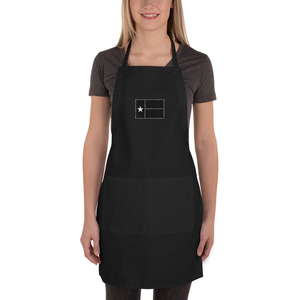 Blonde woman wearing black apron with black Texas flag