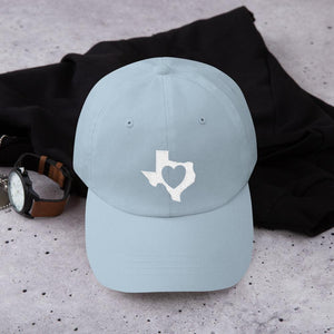 heart in Texas on light blue hat on the counter with a watch