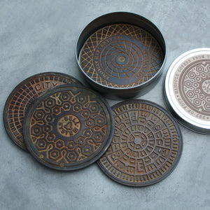 "Cast bronze coasters, 3 7/8"", set of 4. Each piece is uniquely hand patinated to resemble authentic manholes found on the street of Los Angeles. Signed on the reverse."