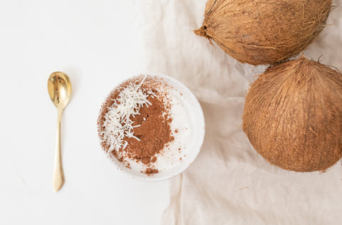 coconut and bowl image of smoothie bowl with gold spoon