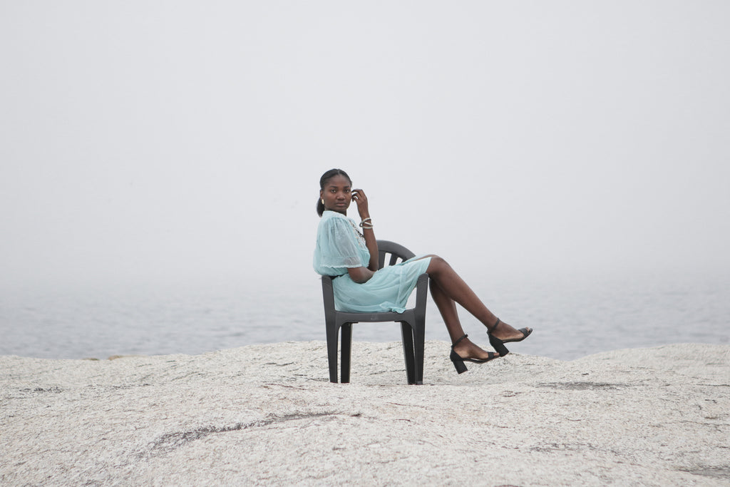 African model sitting on plastic chair at the ocean wearing blue petticoat