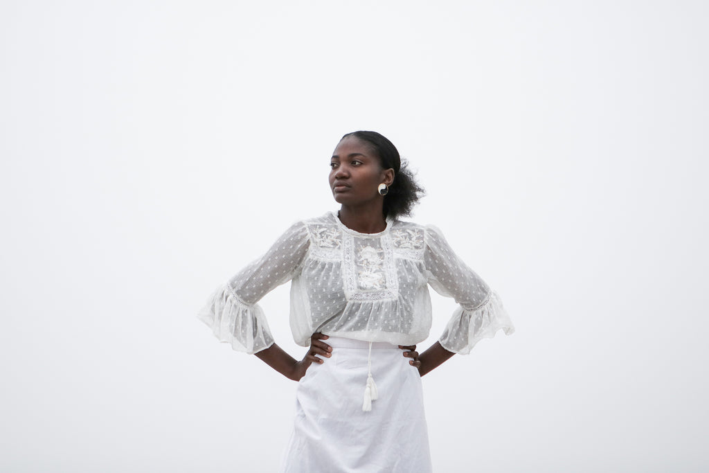 African model wearing white sheer blouse and white linen skirt