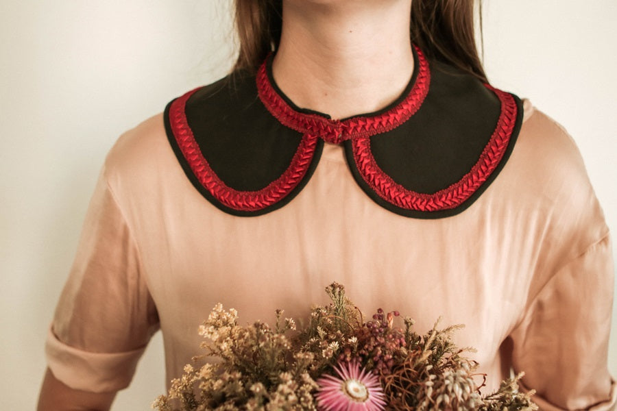 Exaggerated black collar with red trim. Model holding flowers.
