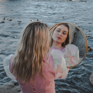 Model holding mirror wearing beautiful pink blouse