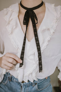 Model holding Black lace choker necklace