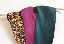 Image is of three wired Celine Martine head wrap with animal print sateen fabric hanging on a branch on white wood panelled wall. The colours are animal print, dark fuchsia and dark teal.