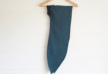 mage is of a wired Celine Martine head wrap in dark teal linen, hanging on a coathanger on white wood panelled wall.mage is of a wired Celine Martine head wrap with animal print sateen fabric hanging on a coat-hanger on white wood panelled wall.