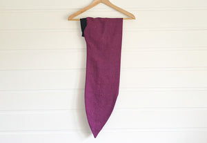 Image is of a wired Celine Martine head wrap wrap in dark fuchsia linen, hanging on a coathanger on white wood panelled wall.
