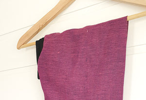 Image is of a wired Celine Martine head wrap wrap in dark fuchsia linen, hanging on a coat-hanger on white wood panelled wall.