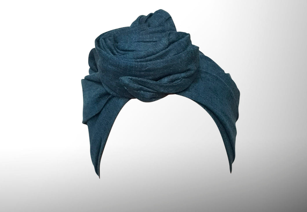 Image is of a dark teal (dyed-yarn) wired Celine Martine headwrap / hair scarf styled as rosette turban on a head with no face