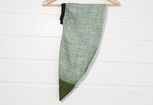 Image is of a wired Celine Martine head wrap / hair scarf in light green muslin on white wood panelled wall.