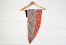 Image is of a wired Celine Martine head wrap / hair scarf in grey graphic with orange tips at the end. It is hanging on a coat-hanger against a white wood panelled wall.