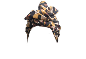 Image is of a wired Celine Martine head wrap with animal print sateen fabric, styled with a fan turban.