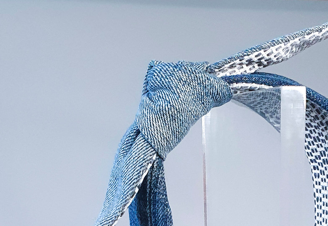 Image is a close-up of a Mathilde Side Knot - in upcycled denim styled upright on a see-through plexiglass stand. White and blue woven lining  can be seen. Background is light blue with shadowing.