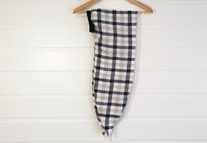 Image is of a wired Celine Martine head wrap in creme / white / navy checked linen, hanging on a coat-hanger on white wood panelled wall.