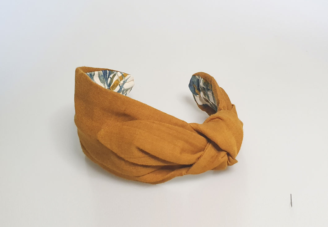 Saffron headband with a side-knot lying on a white surface