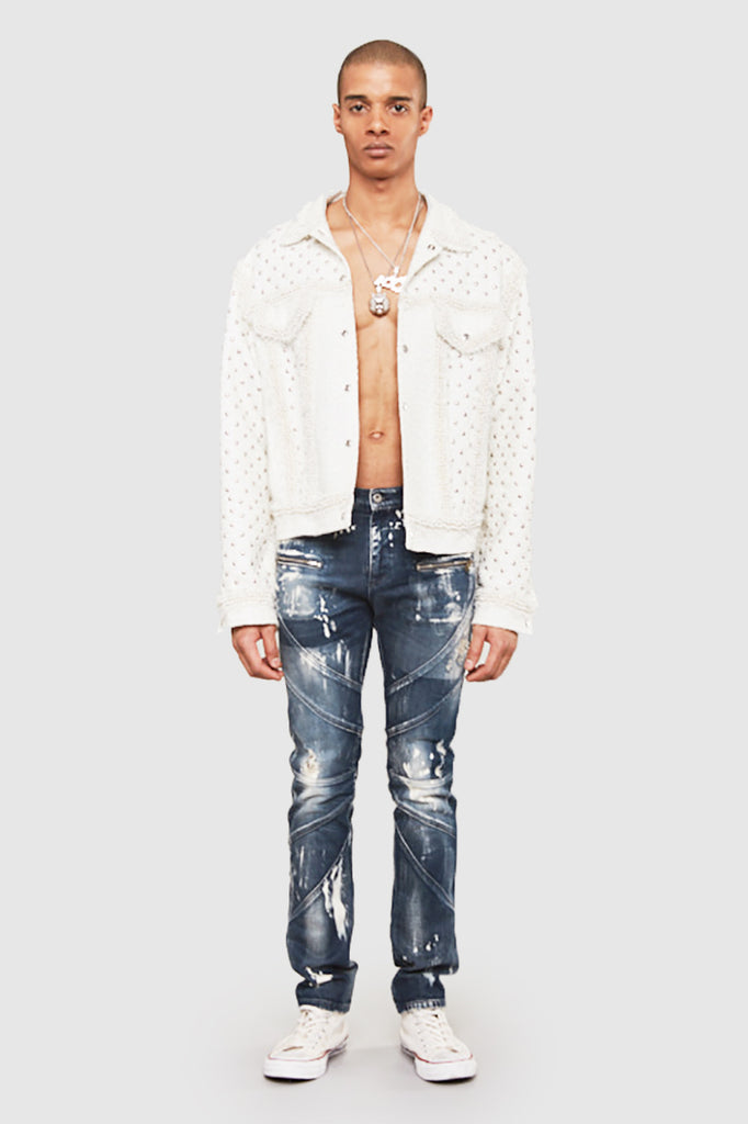 A man is wearing a studded biker denim pants by Faith Connexion, a brand of luxury clothes