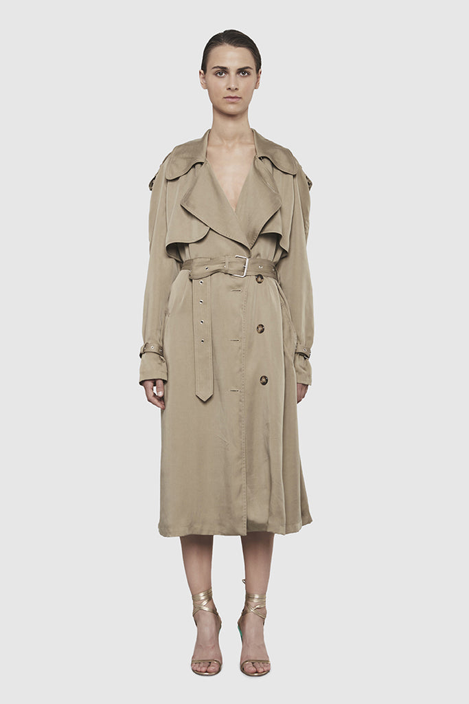 A woman is wearing an oversize trench coat by Faith Connexion, a brand of luxury clothes