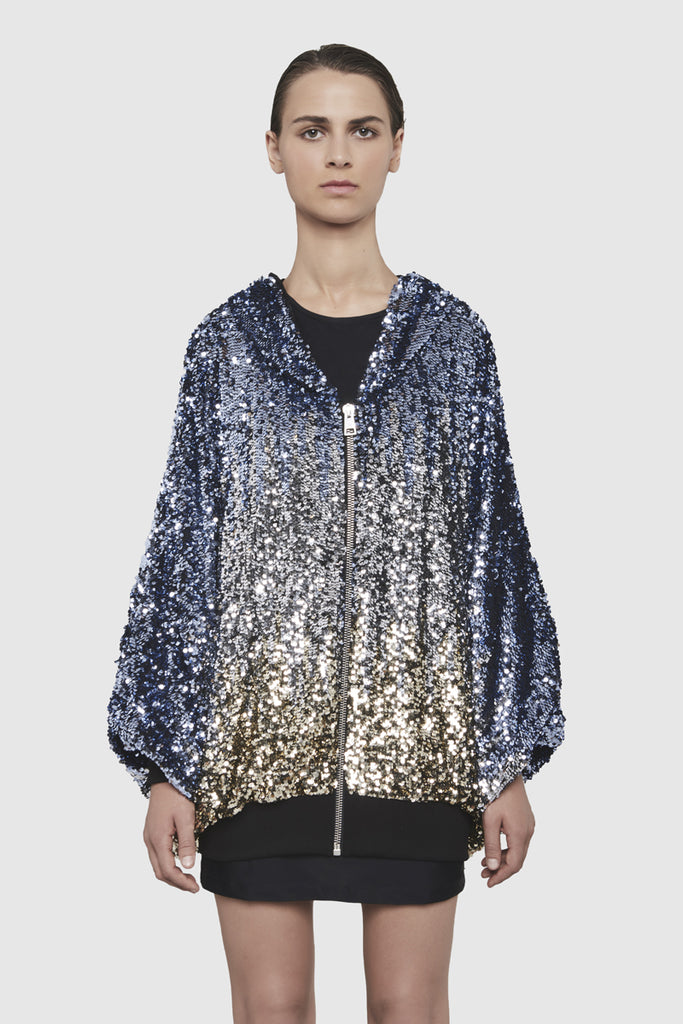 A woman is wearing a sequins hoodie jacket by Faith Connexion, a brand of luxury clothes