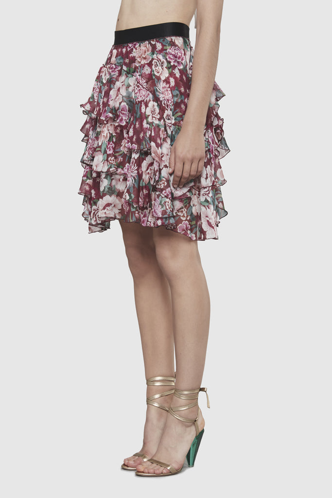 A woman is wearing a flower printed knot skirt by Faith Connexion, a brand of luxury clothes