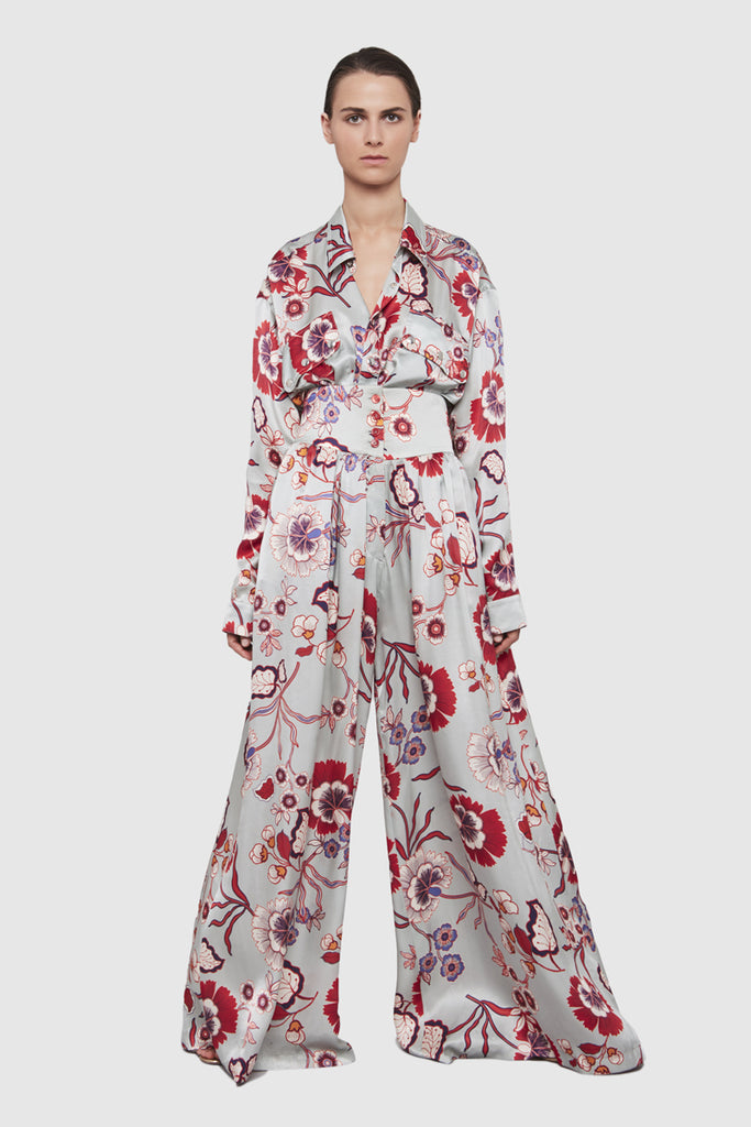 A woman is wearing a silky flower print basque pants by Faith Connexion, a brand of luxury clothes