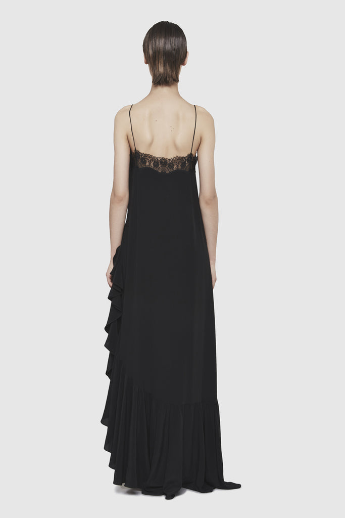A woman is wearing a black silky nightgown dress by Faith Connexion, a brand of luxury clothes