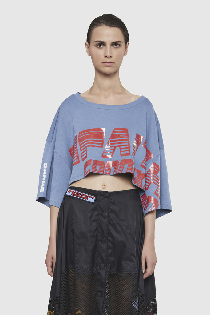 A woman is wearing a Shuko cropped sweatshirt by Faith Connexion, a brand of luxury clothes