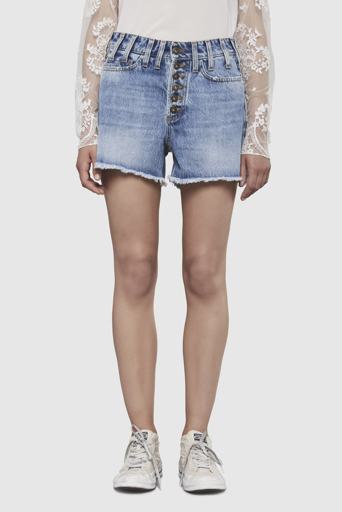 A woman is wearing a NTMB retro denim shorts by Faith Connexion, a brand of luxury clothes