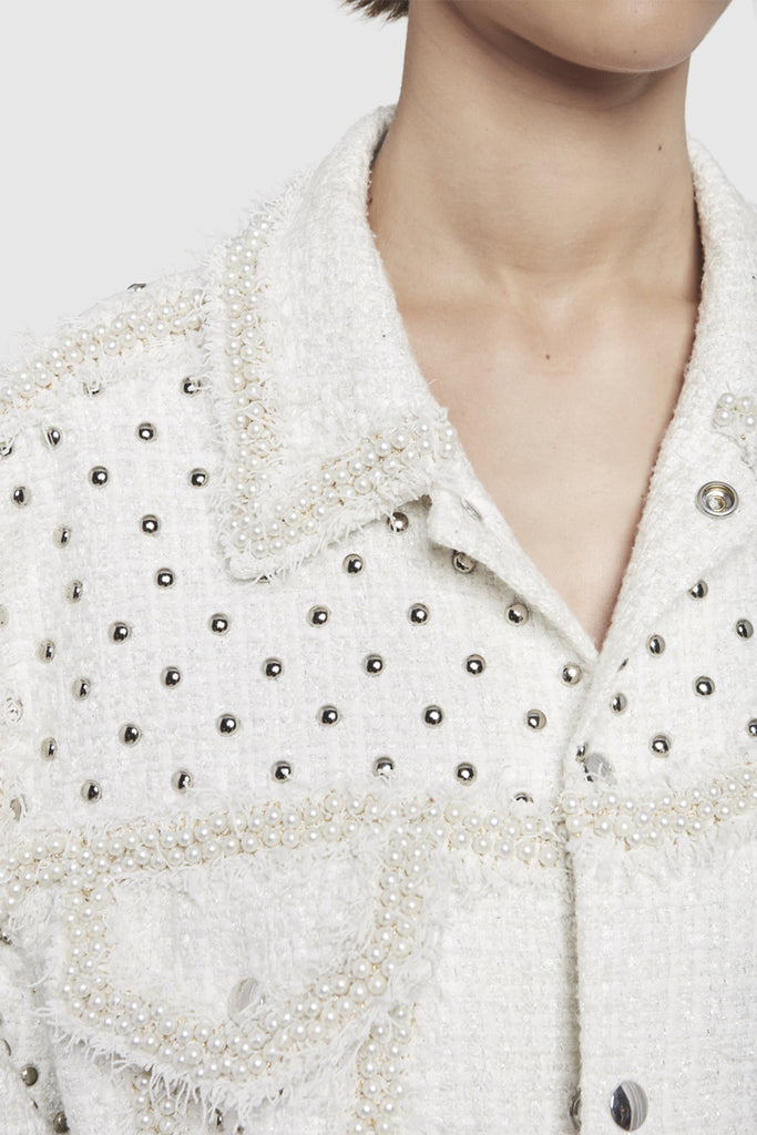 A close-up of a white tweed oversize jacket by Faith Connexion, a brand of luxury clothes