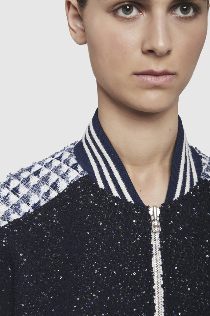 A close-up of a tweed bomber jacket crafted with jersey, tweed and sequin embroidery by Faith Connexion, a brand of luxury clothes