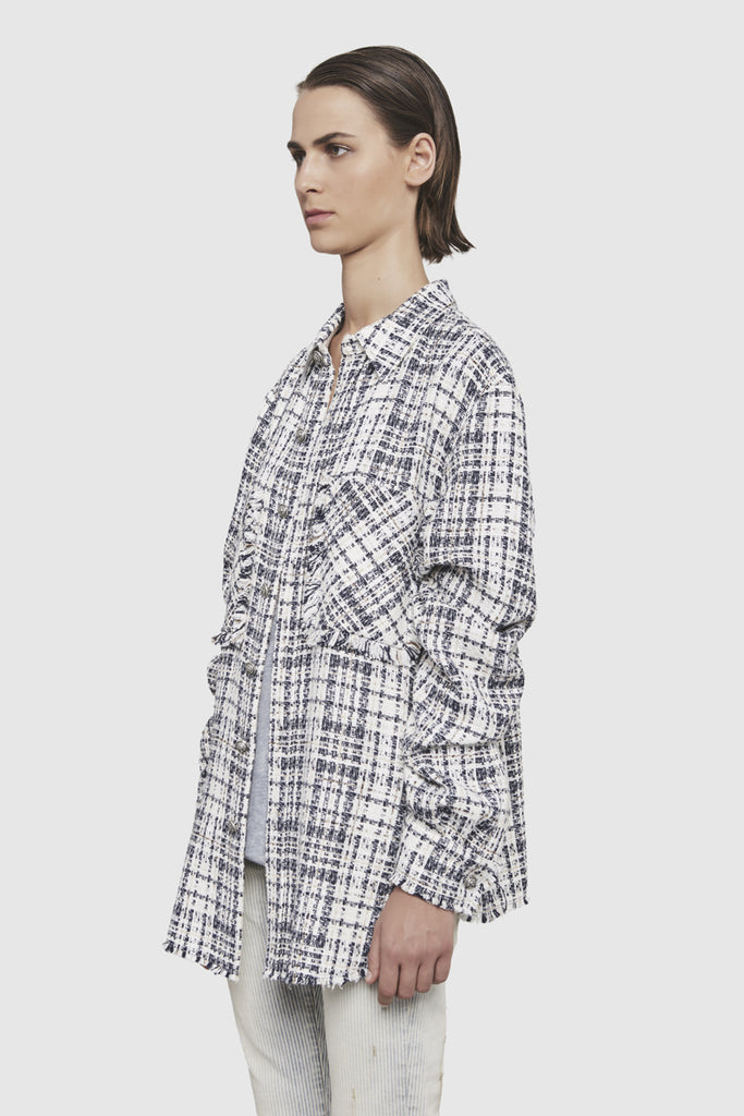 A woman is wearing a checked tweed shirt by Faith Connexion, a brand of luxury clothes