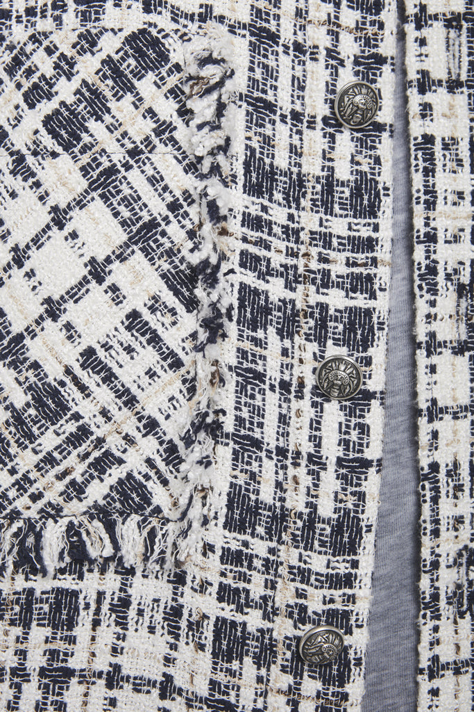 A close-up on the fabric of a checked tweed shirt by Faith Connexion, a brand of luxury clothes