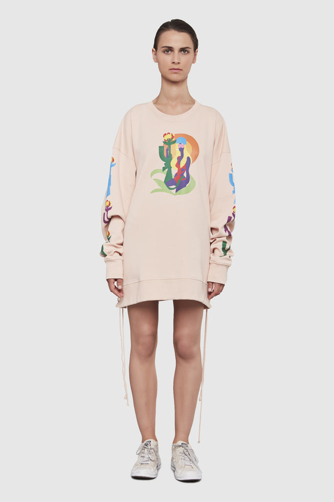 A woman is wearing a Todd James baby pink crewneck sweatshirt by Faith Connexion, a brand of luxury clothes