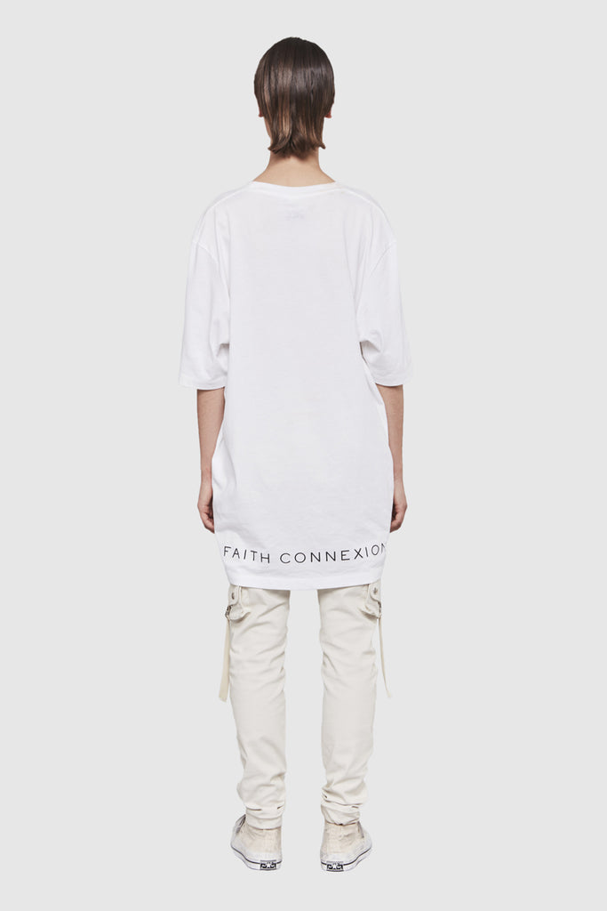 A woman is wearing a white oversize t-shirt by Faith Connexion, a brand of luxury clothes
