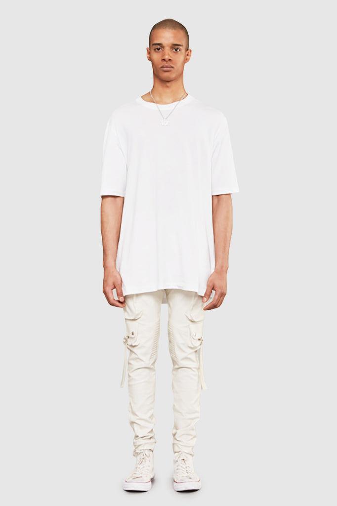 A man is wearing a white oversize t-shirt by Faith Connexion, a brand of luxury clothes