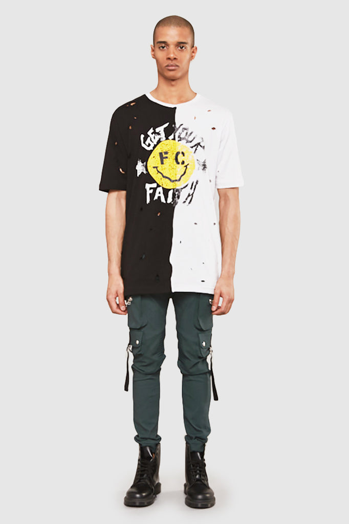 A man is wearing a NTMB split t-shirt with a smiley print by Faith Connexion, a brand of luxury clothes