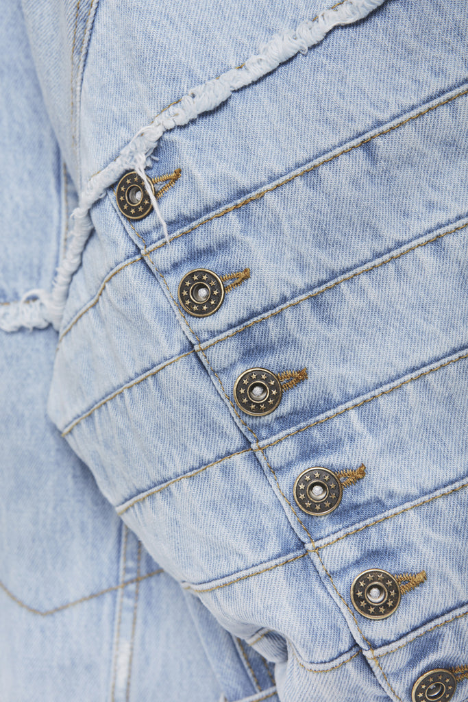 A close-up of a reconstructed denim jacket by Faith Connexion, a brand of luxury clothes